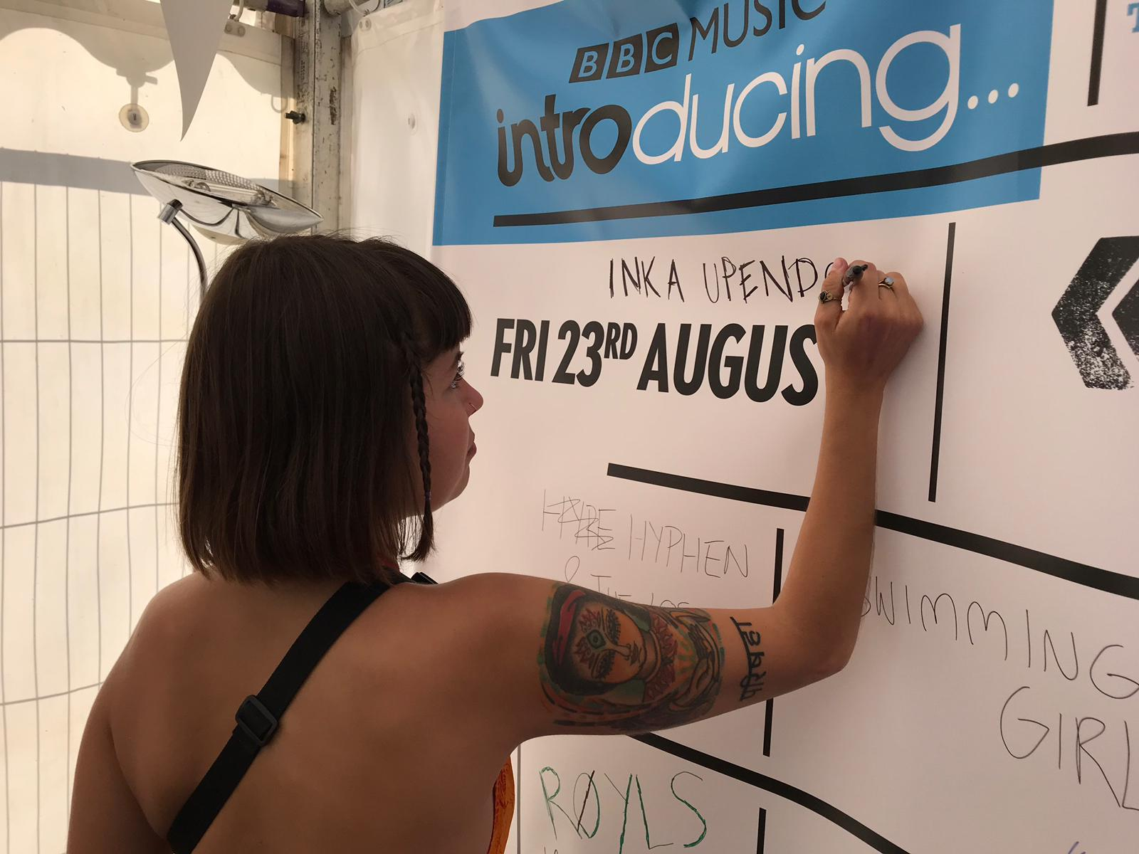 Inka Upendo signing the BBC Introducing at Reading and Leeds 2019 poster